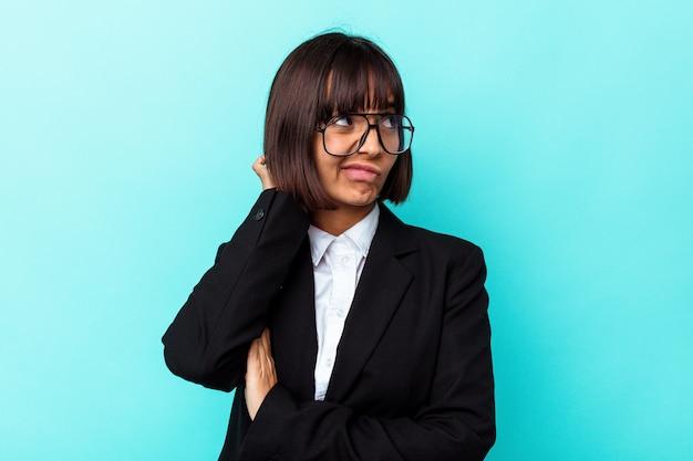 Молодая женщина смешанной расы бизнес, изолированные на синем фоне, касаясь затылка, думая и делая выбор.