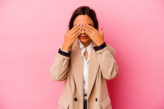 手で目を覆うことを恐れてピンクの背景に分離された若いビジネス混血の女性。