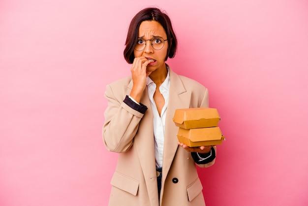 ピンクの背景に爪を噛んで孤立した若いビジネス混血の女性、神経質で非常に心配しています。