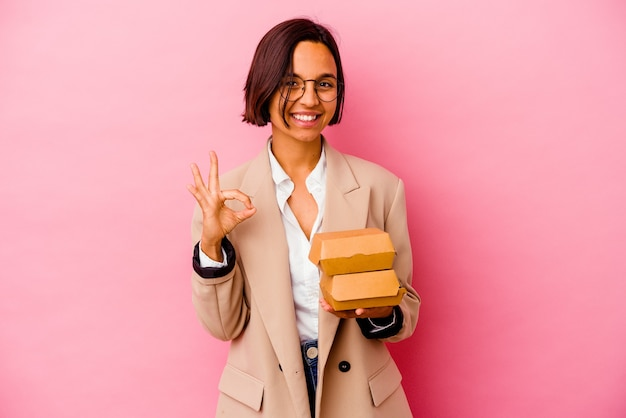 ピンクの背景に分離された若いビジネス混血の女性は、陽気で自信を持って大丈夫なジェスチャーを示しています。
