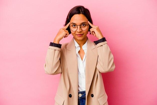 Молодая деловая женщина смешанной расы, изолированная на розовом фоне, сосредоточилась на задаче, держа указательные пальцы, указывая головой.