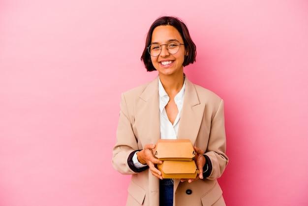 ピンクの背景に分離された若いビジネス混血の女性幸せ、笑顔、陽気な。