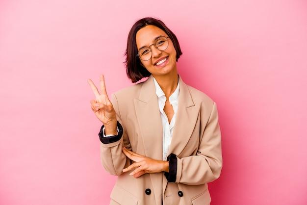 손가락으로 평화 기호를 보여주는 즐겁고 평온한 분홍색 배경에 고립 된 젊은 비즈니스 혼혈 여자.