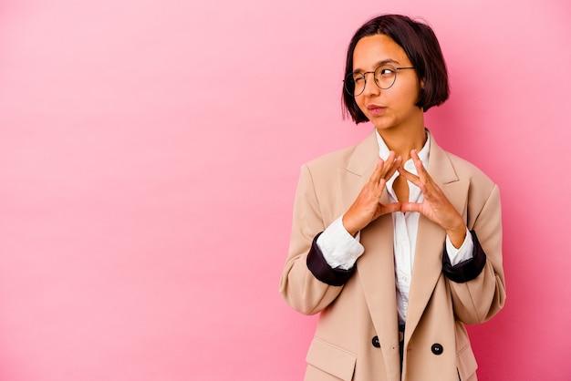 젊은 비즈니스 혼혈 여자 마음에 계획을 만들고, 아이디어를 설정하는 분홍색 배경에 고립.