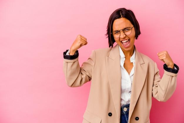 勝利、勝者の概念の後に拳を上げるピンクの背景に分離された若いビジネス混血の女性。