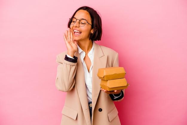 開いた口の近くで叫び、手のひらを保持しているピンクの背景に分離された若いビジネス混血の女性。
