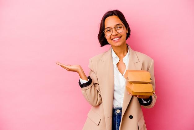 ピンクの背景で隔離の若いビジネス混血の女性は、手のひらにコピースペースを示し、腰に別の手を保持しています。