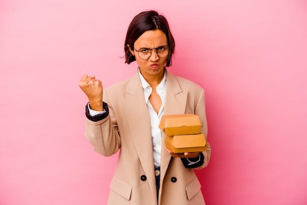 カメラに拳、攻撃的な表情を示すピンクの背景に分離された若いビジネス混血の女性。