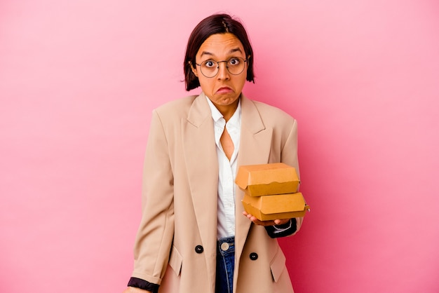 ピンクの背景に分離された若いビジネス混血の女性は肩をすくめると混乱した目を開いています。