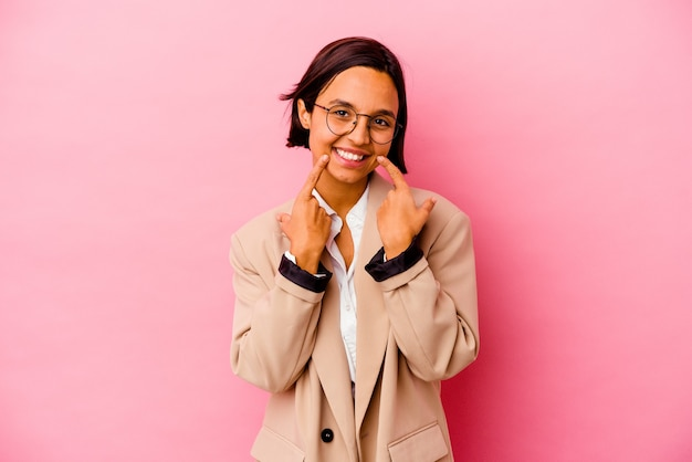 입에서 손가락을 가리키는 분홍색 배경 미소에 고립 된 젊은 비즈니스 혼혈 여자.