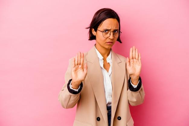 ピンクの背景に孤立した若いビジネス混血の女性は、一時停止の標識を示す伸ばした手で立って、あなたを防ぎます。