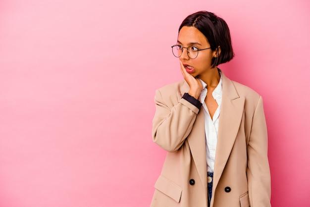 Молодая деловая женщина смешанной расы, изолированная на розовой стене, шокирована из-за чего-то, что она видела.