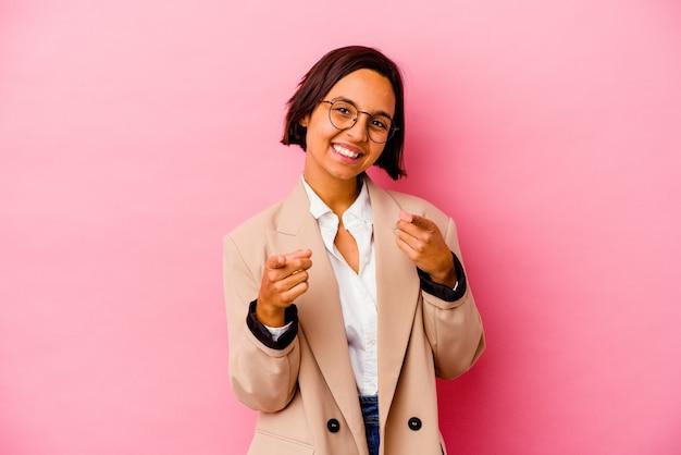 Молодая деловая женщина смешанной расы изолирована на розовой стене с веселыми улыбками, указывая вперед