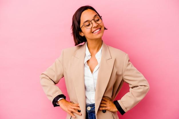 ピンクの壁に孤立した若いビジネス混血の女性は、腰に手を保つことに自信を持っています。