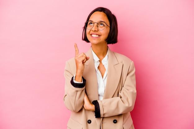 분홍색 벽에 고립 된 젊은 비즈니스 혼혈 여자는 빈 공간을 보여주는 두 앞 손가락으로 나타냅니다