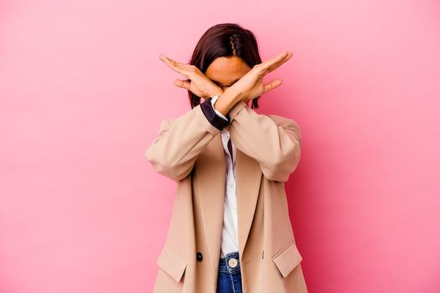 ピンクの壁に孤立した若いビジネス混血の女性は、2つの腕を交差させたまま、概念を否定します。