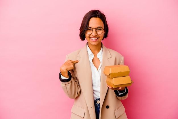 Молодая деловая женщина смешанной расы изолирована на розовой стене человека, указывая рукой на пространство для копирования рубашки, гордая и уверенная