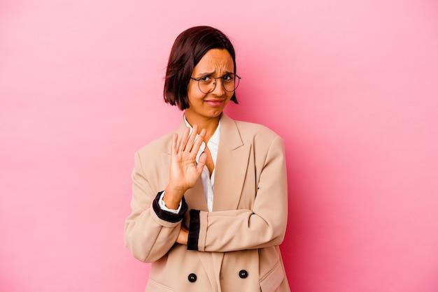 Молодая деловая женщина смешанной расы изолирована на розовой стене, отвергая кого-то, показывающего жест отвращения.