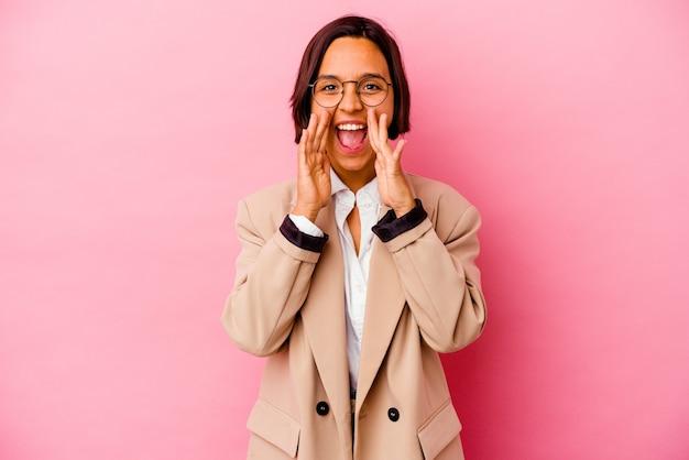 ピンクの壁に孤立した若いビジネス混血の女性が正面に興奮して叫んでいます。