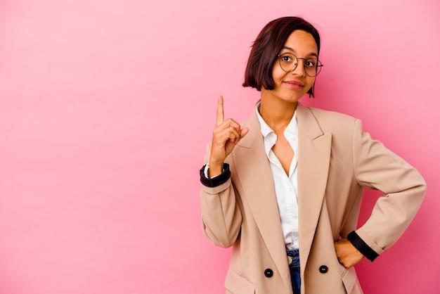 손가락으로 번호 하나를 보여주는 분홍색 벽에 고립 된 젊은 비즈니스 혼혈 여자.