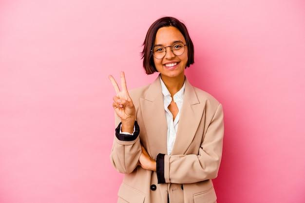 ピンクの壁に分離された若いビジネス混血の女性は、指で2番目を示しています。