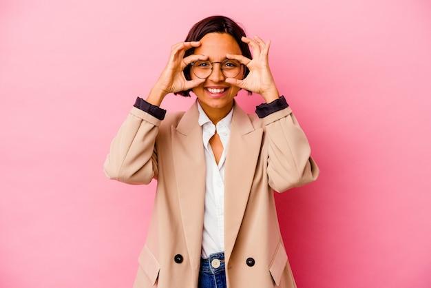 ピンクの壁に分離された若いビジネス混血の女性