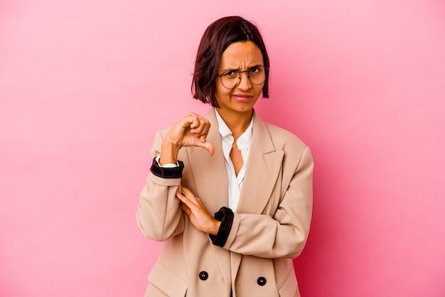 Молодая женщина смешанной расы бизнеса изолированная на розовой стене показывая большой палец руки вниз, концепцию разочарования.