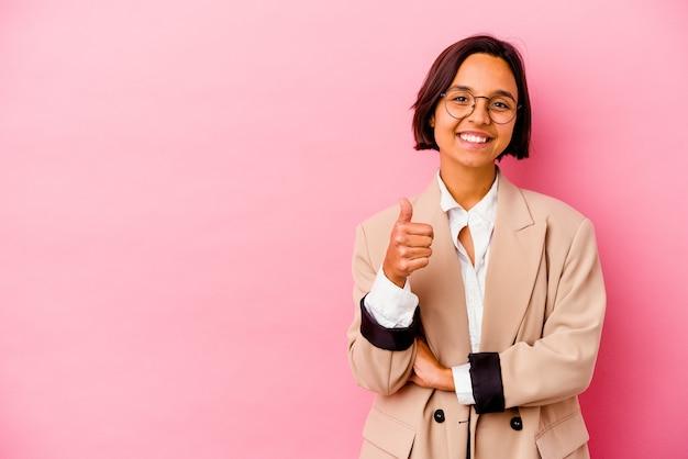 ピンクの壁に分離された若いビジネス混血の女性笑顔と親指を上げる