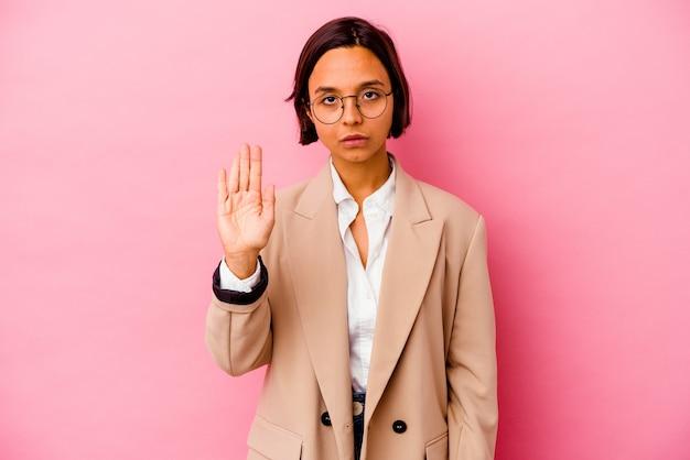 ピンクの壁に孤立した若いビジネス混血の女性は、一時停止の標識を示す伸ばした手で立って、あなたを防ぎます。