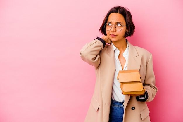 頭の後ろに触れて、考えて、選択をするピンクの壁に孤立した若いビジネス混血の女性。