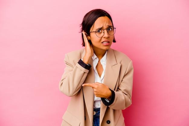 ゴシップを聴こうとしているピンクの壁に孤立した若いビジネス混血の女性。
