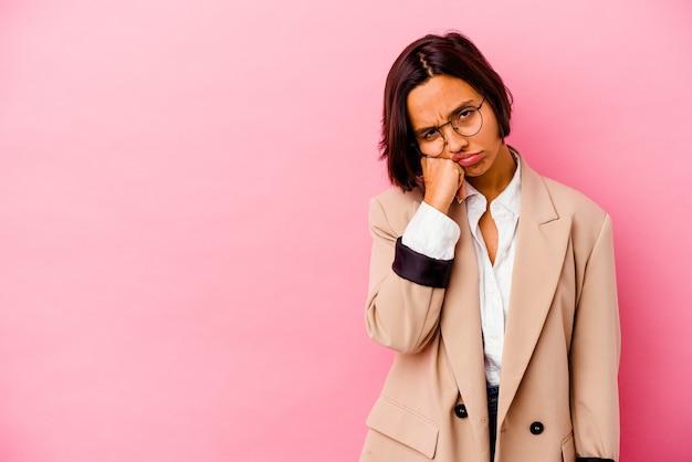 コピースペースを見て、悲しくて物思いにふけるピンクの壁に孤立した若いビジネス混血の女性。
