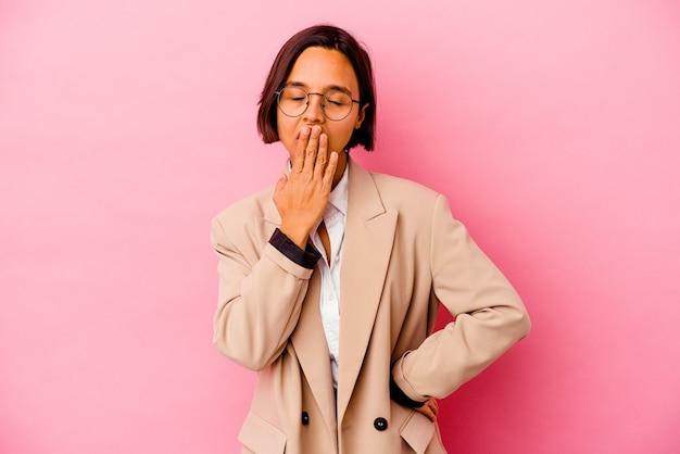 ピンクの壁のあくびで孤立した若いビジネス混血の女性は、手で口を覆う疲れたジェスチャーを示しています。