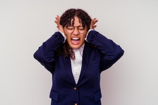 若いビジネスの混血の女性は、大きな音を聞かないように手で耳を覆う白い背景に隔離されました。