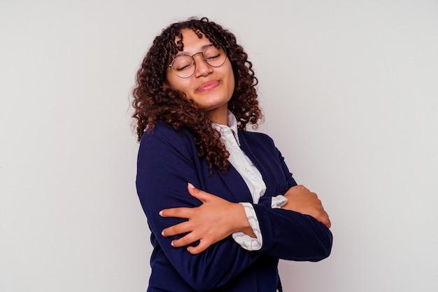 흰색 배경에 고립 된 젊은 비즈니스 혼혈 여자 포옹, 평온하고 행복 미소.