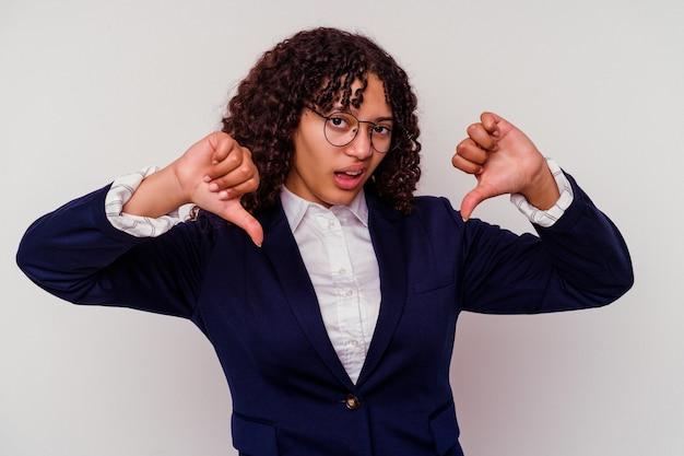 Молодая женщина смешанной расы бизнес, изолированные на белом фоне, показывая большой палец вниз и выражая неприязнь.