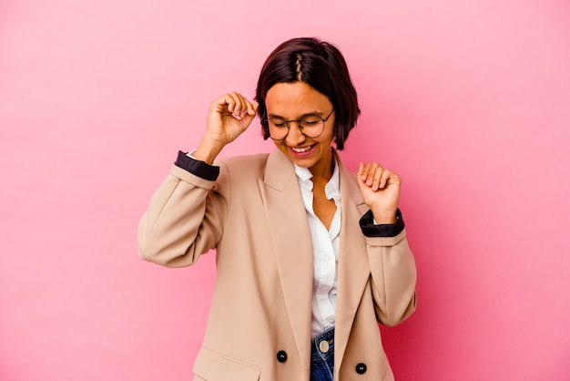 Young business mixed race woman isolated on pink background celebrating a special day, jumps and raise arms with energy.