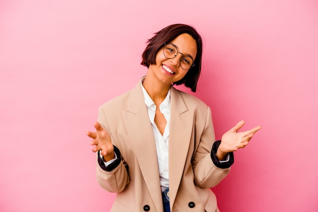 Young business mixed race woman isolated on pink background feels confident giving a hug to the camera.