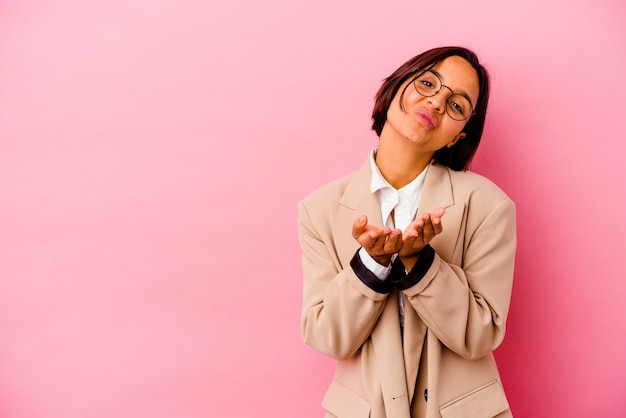 Young business mixed race woman isolated on pink background folding lips and holding palms to send air kiss.
