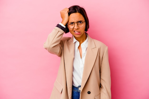 Young business mixed race woman isolated on pink background forgetting something, slapping forehead with palm and closing eyes.