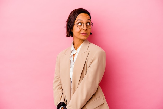 Young business mixed race woman isolated on pink background relaxed and happy laughing, neck stretched showing teeth.