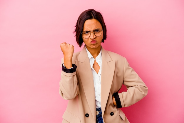 Young business mixed race woman isolated on pink background showing fist to camera, aggressive facial expression.
