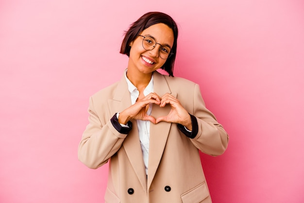 Young business mixed race woman isolated on pink background smiling and showing a heart shape with hands.