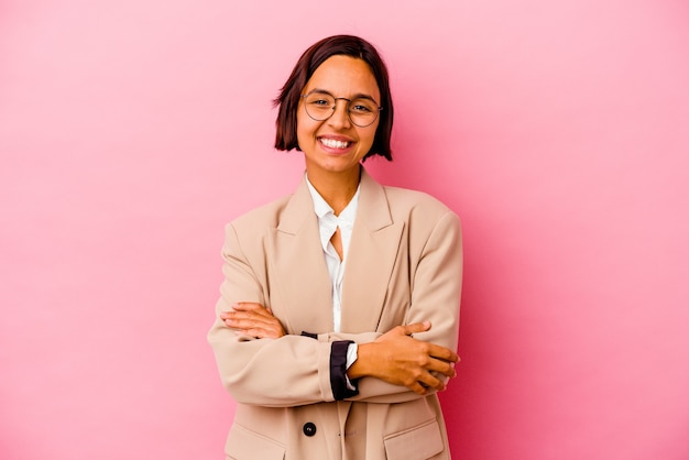Young business mixed race woman isolated on pink background who feels confident, crossing arms with determination.