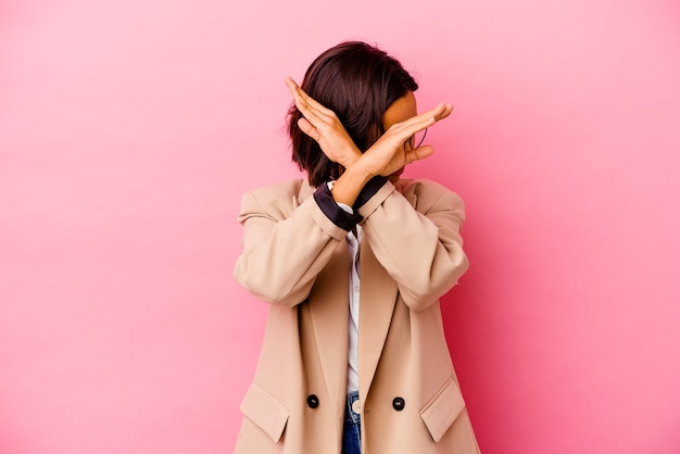 Young business mixed race woman isolated on pink wall keeping two arms crossed, denial concept.