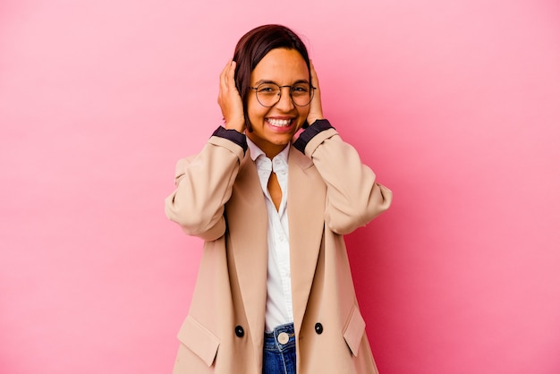 Young business mixed race woman isolated on pink wall laughs joyfully keeping hands on head