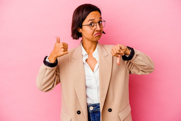 Young business mixed race woman isolated on pink wall showing thumbs up and thumbs down, difficult choose concept