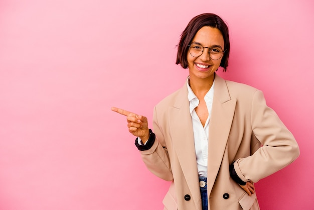 Young business mixed race woman isolated on pink wall smiling cheerfully pointing with forefinger away