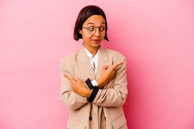 분홍색 포인트 옆에 젊은 비즈니스 혼혈 여성은 두 가지 옵션 중에서 선택하려고합니다.