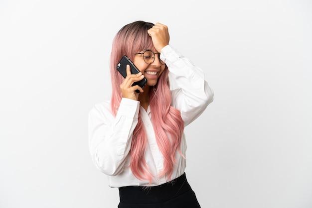 Молодая деловая женщина смешанной расы с розовыми волосами, держащая мобильный телефон на розовом фоне, кое-что поняла и намеревается найти решение